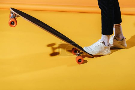 cropped view of stylish man in white sneakers with longboard, on yellow