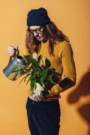 Photo pour Homme élégant avec les cheveux longs arrosage plante verte, sur jaune - image libre de droit