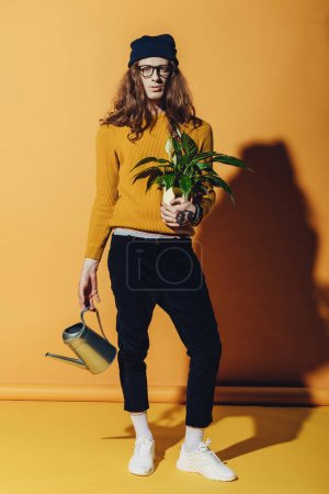 fashionable male model posing with watering can and plant, on yellow
