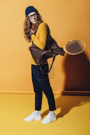 handsome man with vintage backpack and wooden tennis racket, on yellow