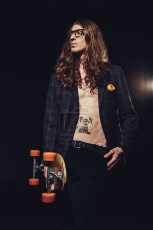 handsome skater with long hair posing with longboard, isolated on black with backlit