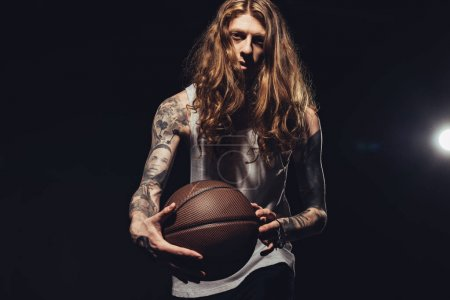 stylish tattooed man with basketball ball, isolated on black with backlit