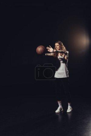 man playing with basketball ball, on black