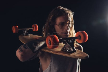 handsome skateboarder with long hair holding longboard, isolated on black