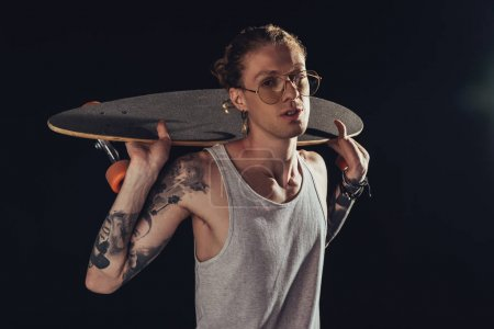 fashionable tattooed man in stylish glasses posing with longboard, isolated on black