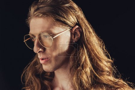fashionable man with long hair in trendy eyeglasses, isolated on black