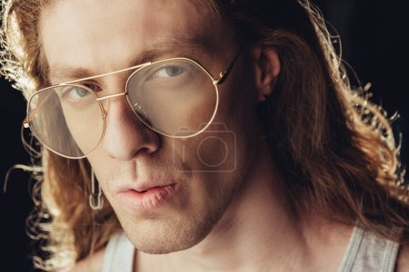 portrait of fashionable man with long hair in trendy glasses, isolated on black