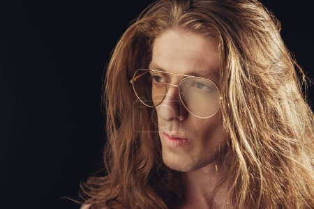 portrait of stylish man with long hair in stylish glasses, isolated on black