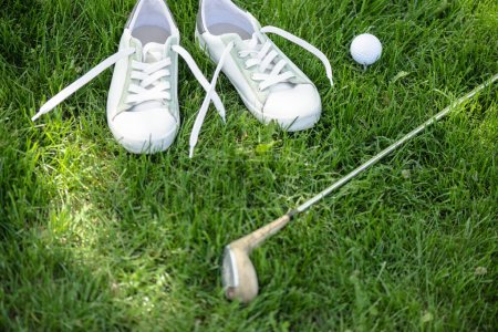 close up view of golf equipment and white shoes on green pitch