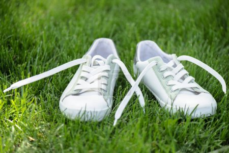close up view of white stylish  shoes on green grass