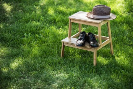 close up view of arranged black leather shoes and straw hat on wooden stairs on grassland