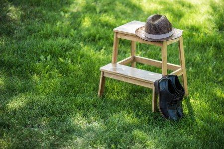 Photo pour Vue rapprochée de chaussures en cuir noir disposées et chapeau de paille sur les escaliers en bois sur les prairies - image libre de droit