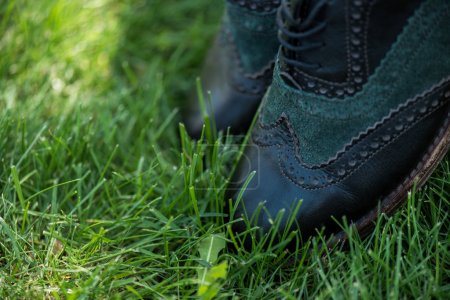 selective focus of black leather shoes on green grass