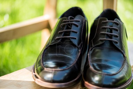 selective focus of black leather shoes on wooden stairs with green blurred background