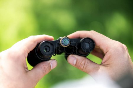 cropped shot of man holding binoculars on blurred green background