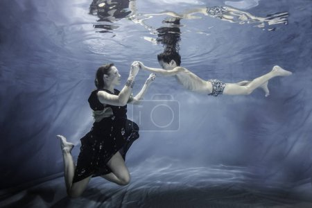 Pregnant woman posing with olderson posing underwater