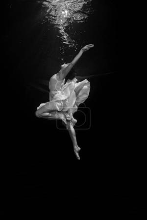 A young ballerina is dancing underwater