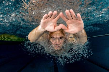 Young swimmer swimming in a pool underwater