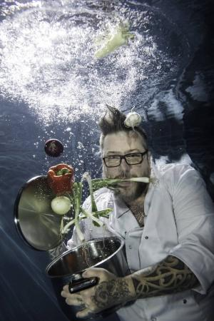 A tattooed chef posing with vegetables underwater