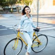 Lovely woman with a yellow bicycle on the road...
