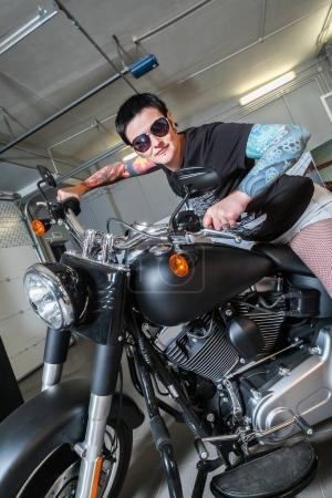 Cool sensual biker girl sitting on old fashioned motorcycle in garage interior on grey wooden wall background, vertical picture