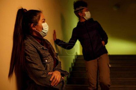 Ein junges asiatisches und afrikanisches Mädchen in medizinischen Einweg-Schutzmasken versteckt sich vor mit dem Virus infizierten Menschen im Treppenhaus. Rettung vor einer Virusinfektion. Interracial internationale Hilfe, fr