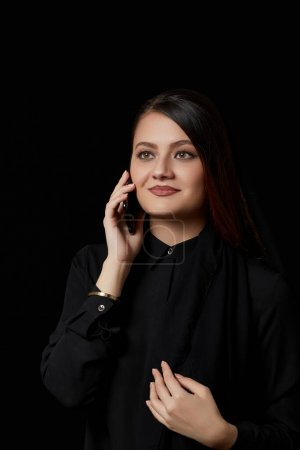 Photo for A young beautiful Muslim woman in black clothes uses a mobile phone.smiling, texting, talking. on a black isolated background. - Royalty Free Image