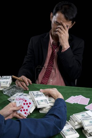 The young gambler use hand off the face and stressed when conten