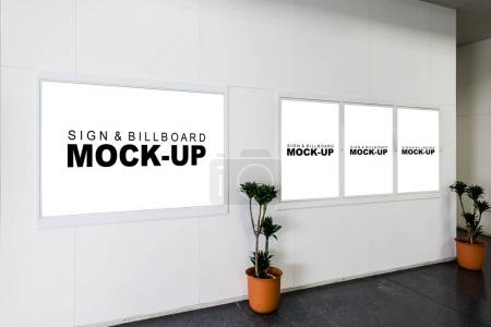 Photo for The billboard and signboard at the wall, blank space white display with frame in subway for advertising with clipping path, Decorated with potted tree placed forward - Royalty Free Image