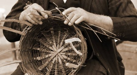 man creates a straw basket with sepia toned effect
