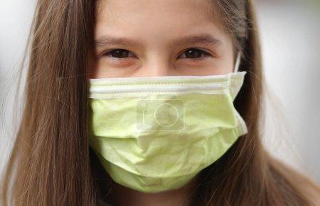jeune fille aux longs cheveux bruns porte un masque chirurgical pour se protéger du terrible et contagieux virus Corona