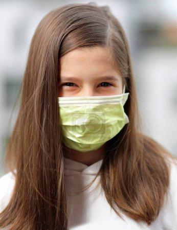 jeune fille aux longs cheveux bruns porte un masque chirurgical pour protéger les voies respiratoires contre le virus Corona