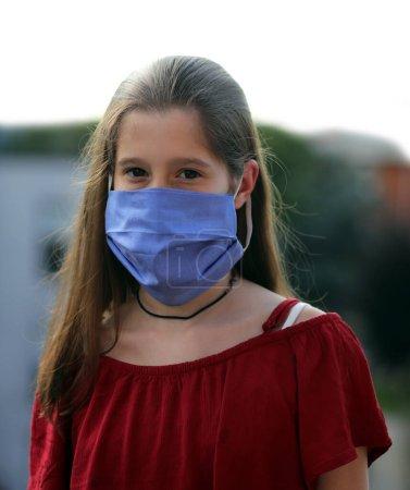 Belle jeune fille aux cheveux longs et masque de chirurgien bleu pendant le confinement causé par le Coronavirus mortel également appelé Covid-19