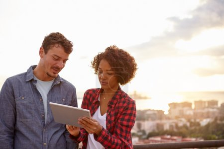 Foto de Pareja buscando intensamente a una tableta con un scape de la ciudad detrás de ellos y una magnífica puesta de sol mientras usa ropa casual - Imagen libre de derechos