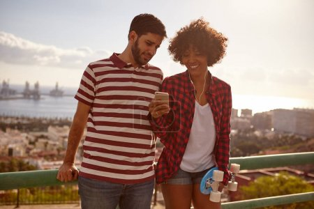 Photo for Young couple looking at smartphone standing on bridge against city background - Royalty Free Image