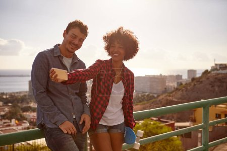 Photo for Laughing couple posing with cell phone for selfie on city background - Royalty Free Image