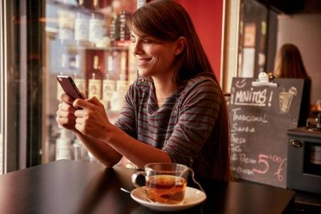 Smiling young woman texting