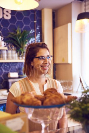 woman standing behind coffee shop counter