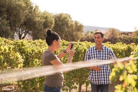 Photo pour Brune prend des photos de l'homme en chemise à carreaux sur une belle journée dans le vignoble - image libre de droit