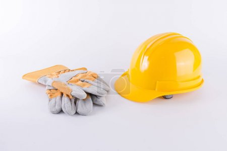 Photo for Yellow safety helmet and Safety gloves on white background. Hard hat and thick gloves on white isolated background. Safety equipment concept. Worker and Industrial theme. - Royalty Free Image