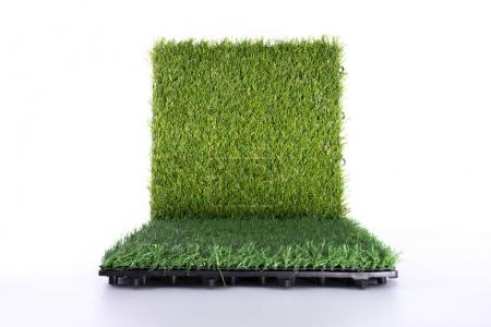 Grass mat on white background. Artificial turf tile background. Object and background concept.