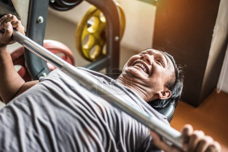 Asian young man doing weight lifting with barbell in fitness gym sport club. Sport and Body build up concept. Strength and muscular training concept. Funny and effort theme.