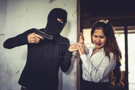Un voleur force une femme à voler son collier d'or à la main dans un coin du bâtiment. Peur des femmes face aux voleurs. Concept pénal de crise sexuelle et de violence illégale