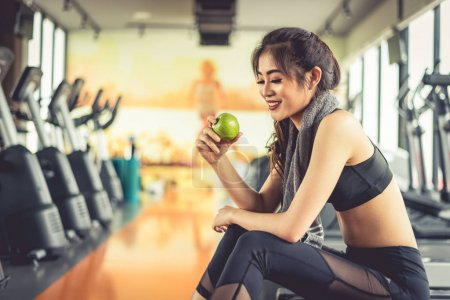 Asian woman holding and looking green apple to eat...