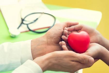 Photo pour Main du docteur donner coeur rouge aux petits enfants de patients pour récupérer de la maladie. Concept d'hôpital et des soins de santé. - image libre de droit