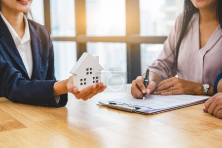 Photo for Real estate broker agent offer private home to customer before sign contract agreement documents for rental house property. Ownership realty purchase. Mortgage loan approval concept. Money investment - Royalty Free Image