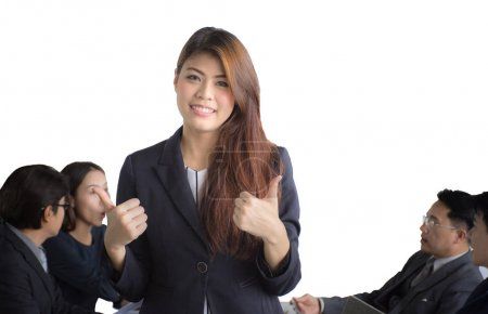 Portrait of Asian businesswoman standing in front of her team at office, female leader