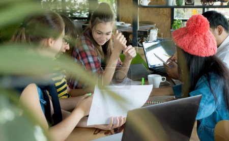 Group of teenage friends working and meeting in team with reports