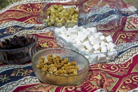 traditional dried fruits of mulberry, plum and white sugar cubes on Armenian traditional carpet with traditional ornaments and patterns at Mulberry festival in Karahunj village, Armenia