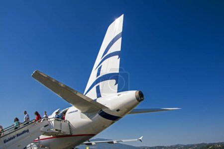 Corfu, Greece - August 25, 2017: tail of the landed airplane Airbus A320 and the passengers leaving the board against the blue sky